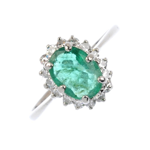 557 - An 18ct gold emerald and diamond cluster ring. The oval-shape emerald, with a single-cut diamond sur...