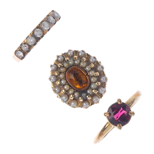 561 - Three 9ct gold gem-set rings. To include a garnet single-stone ring, an orange paste and seed and sp...