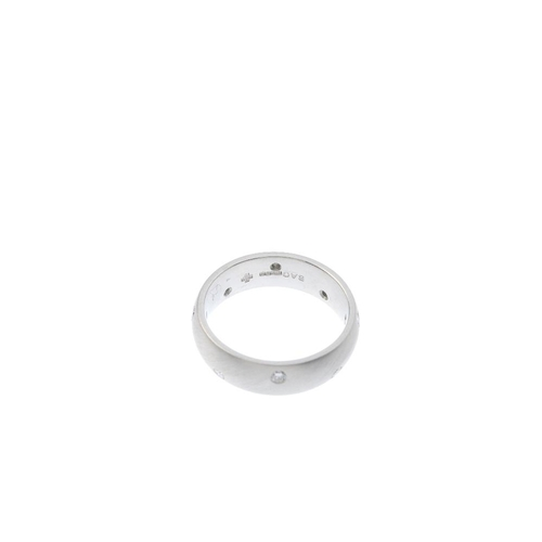 562 - A platinum and diamond band ring. Designed as a series of scattered brilliant-cut diamonds, inset in...