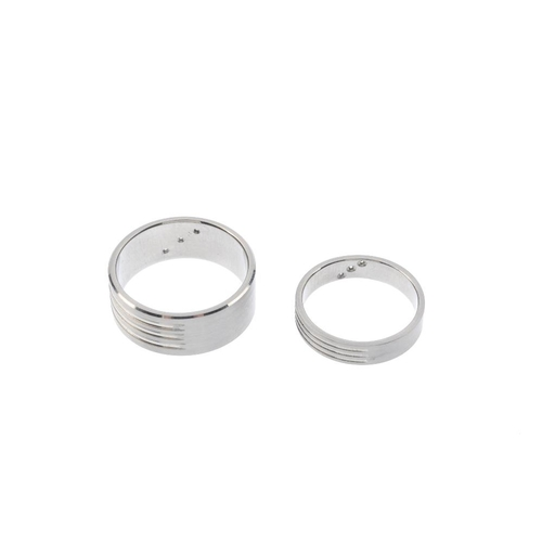 565 - Two palladium and diamond band rings. Each designed as a brilliant-cut diamond diagonal line, inset ...