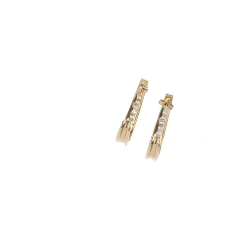 570 - A pair of 9ct gold diamond earrings. Each designed as a graduated brilliant-cut diamond curved line,...