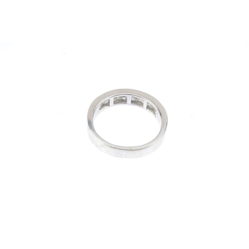 586 - A diamond half-circle eternity ring. The square-shape diamond ring, with plain half-band. Estimated ...