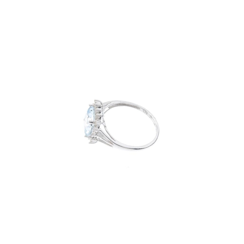 606 - A 9ct gold aquamarine and diamond cluster ring. The cushion-shape aquamarine, within a single-cut di...