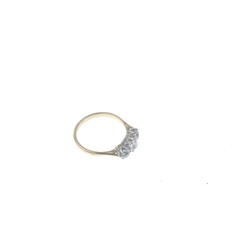 615 - A mid 20th century 18ct gold diamond three-stone ring. The graduated old-cut diamond line, with bi-c...