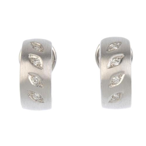 624 - A pair of diamond earrings. Each designed as a textured half-hoop, with an inset brilliant-cut diamo...