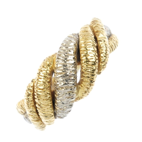626 - A 1970s 18ct gold dress ring. Of bi-colour design, the intertwined textured lines and grooved band. ...