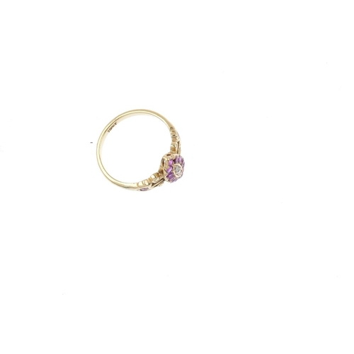 628 - An early 20th century gold ruby and diamond dress ring. The graduated diamond line, with ruby marqui...