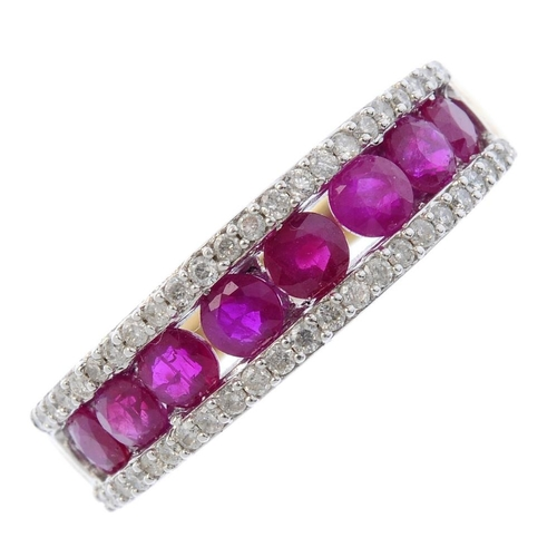 63 - A 9ct gold ruby and diamond half-circle eternity ring. The graduated circular-shape ruby line, with ...