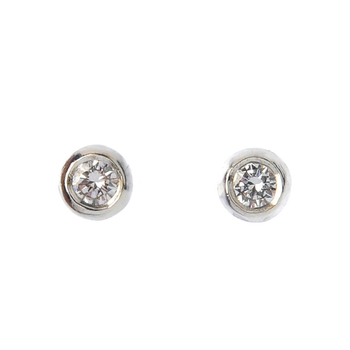 632 - A pair of 18ct gold brilliant-cut diamond collet stud earrings. Estimated total diamond weight 0.15c...