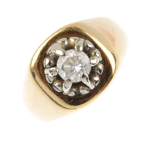 64 - A diamond single-stone ring. Of bi-colour design, the brilliant-cut diamond, with grooved surround a...