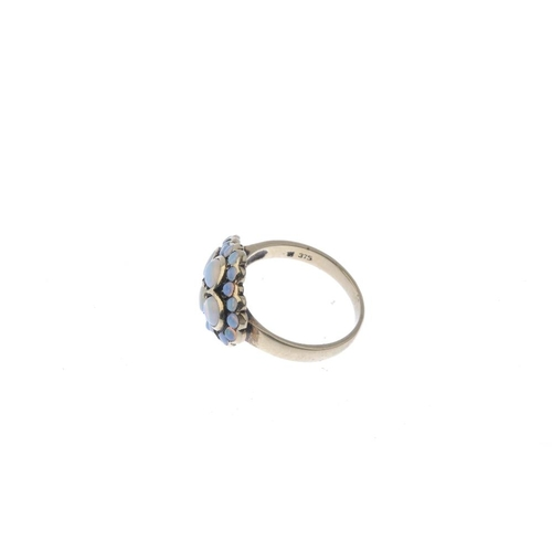 642 - An opal cluster ring. The circular-shape opal cabochon quatrefoil, with similarly-shaped opal caboch...