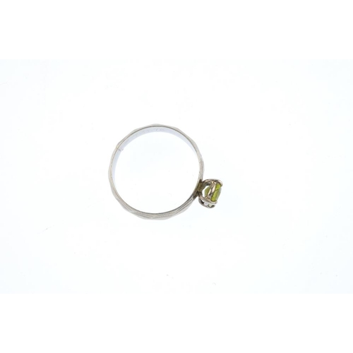 656 - A 1970s 18ct gold peridot single-stone ring. The oval-shape peridot, atop a grooved band. Hallmarks ...