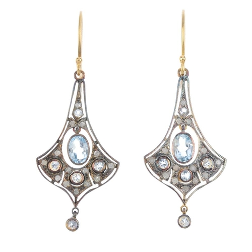 657 - A pair of topaz and diamond earrings. Each designed as an oval-shape blue topaz collet, within a cir...