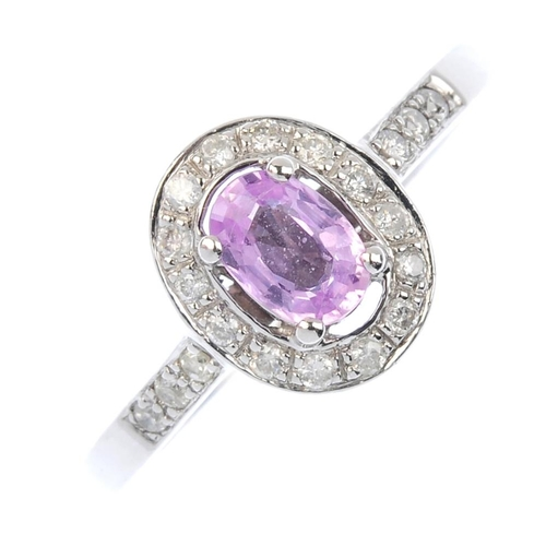 66 - A sapphire and diamond cluster ring. The oval-shape pink sapphire, with brilliant-cut diamond surrou...