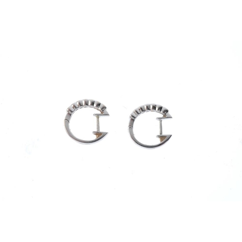 676 - A pair of 18ct gold diamond hoop earrings. Each designed as a series of brilliant-cut diamond collet...