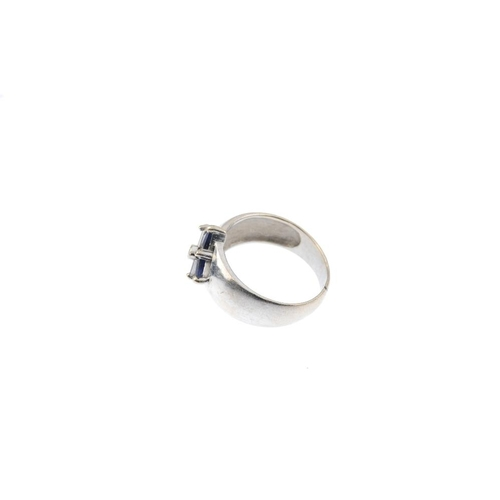 690 - A sapphire and diamond dress ring. Designed as a brilliant and baguette-cut diamond cross, within a ...