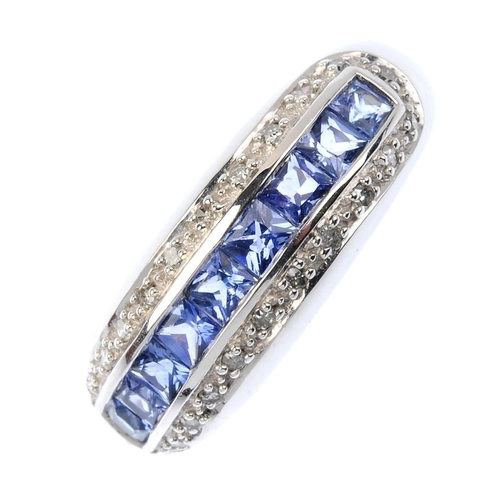 692 - A 9ct gold sapphire and diamond dress ring. The square-shape sapphire line, within a single-cut diam...