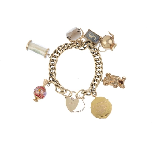 697 - A 9ct gold charm bracelet. The curb-link chain, suspending seven charms, to include a football medal...