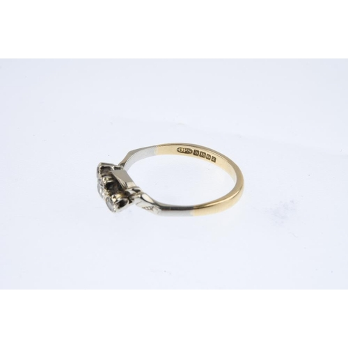 703 - An 18ct gold diamond three-stone crossover ring. The graduated circular-cut diamonds, with textured ...
