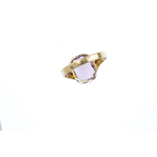 718 - A paste single-stone ring. The cushion-shape purple paste, with openwork tapered shoulders. Ring siz...