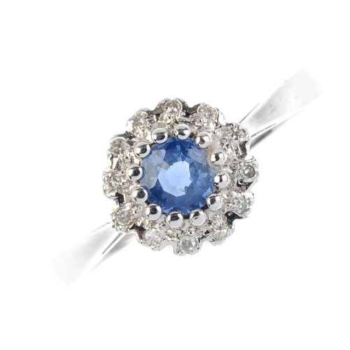 72 - A 9ct gold sapphire and diamond cluster ring. The circular-shape sapphire, within a single-cut diamo...