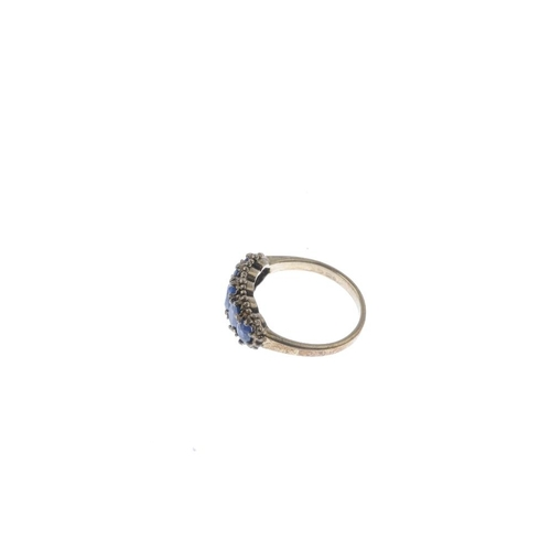 724 - A 9ct gold sapphire five-stone ring. The graduated oval-shape sapphire line, with bead accent surrou...