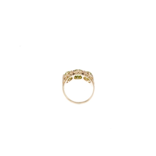 742 - A 9ct gold peridot three-stone ring. The circular-shape peridot slightly graduated line, with scroll...