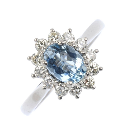 752 - An 18ct gold aquamarine and diamond cluster ring. The oval-shape aquamarine, within a brilliant-cut ...