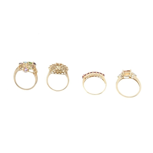 753 - Four 9ct gold gem-set rings. To include a citrine cluster ring, a garnet half-circle eternity ring, ...