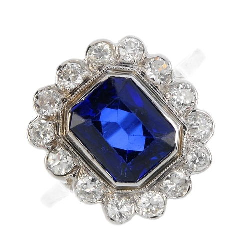 76 - A synthetic sapphire and diamond cluster ring. The rectangular-shape synthetic sapphire, with brilli...