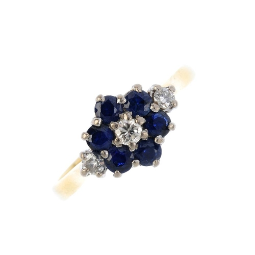 771 - A sapphire and diamond cluster ring. The brilliant-cut diamond, with circular-shape sapphire surroun...