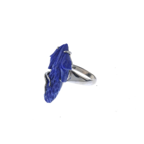 775 - A lapis lazuli dress ring. The lapis lazuli, carved to depict a flower, to the tapered band. Ring si...