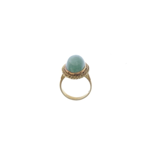 781 - An aventurine quartz dress ring. The oval aventurine quartz cabochon, within a double rope-twist sur...