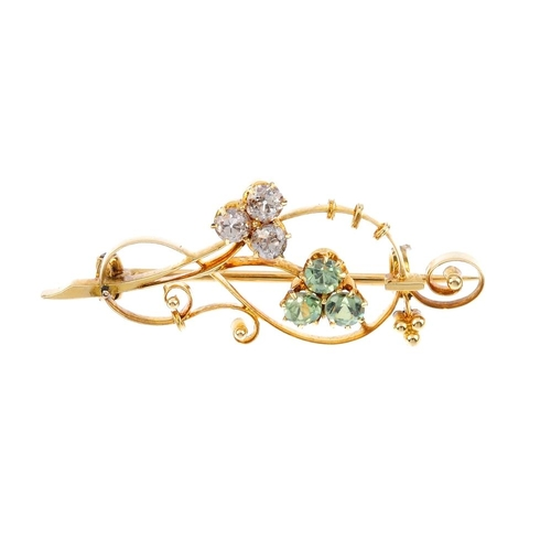 786 - An early 20th century gold diamond and garnet brooch. The garnet and diamond trefoils, to the scroll...