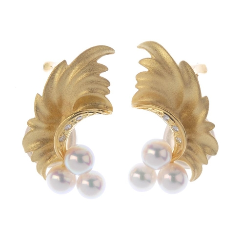 790 - A pair of cultured pearl ear clips. Each designed as a cultured pearl trefoil, with undulating folia...