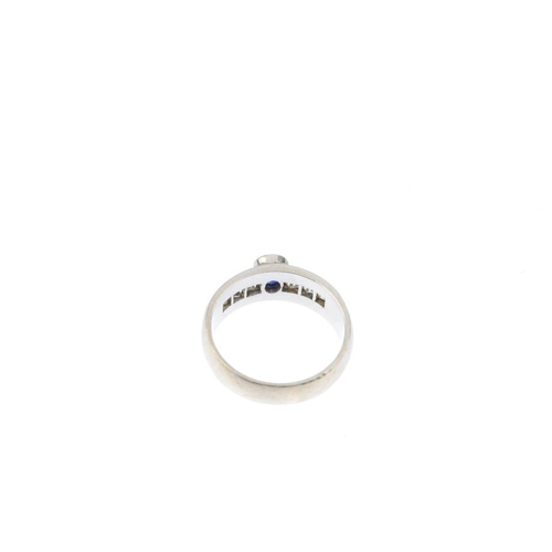 792 - A gem-set ring. The oval-shape sapphire, with channel-set colourless-gem shoulders. Ring size O. Wei...