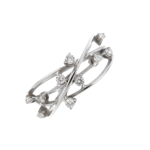 808 - A diamond dress ring. Of openwork design, the three interwoven wires, with brilliant-cut diamond acc...