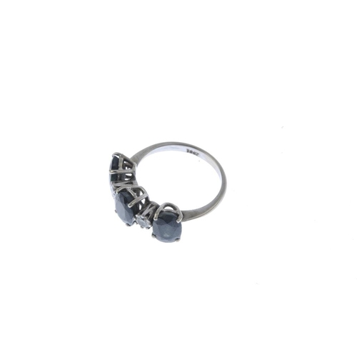 809 - A sapphire and diamond three-stone ring. The oval-shape sapphire line, with brilliant-cut diamond sp...