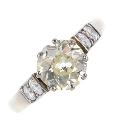811 - A diamond single-stone ring. The circular-cut diamond, with similarly-cut diamond sides inset into a...