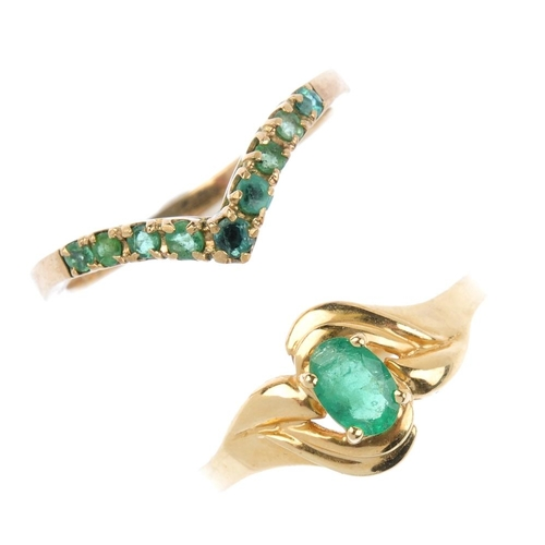 834 - Two emerald rings. The first designed as an oval emerald single-stone crossover, the second designed...