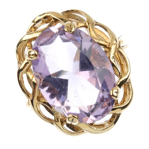 842 - A 9ct gold amethyst single-stone ring. The oval-shape amethyst, with scrolling openwork surround. Ha...
