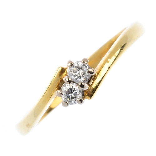851 - An 18ct gold diamond two-stone ring. The brilliant-cut diamond duo, with crossover shoulders. Total ...