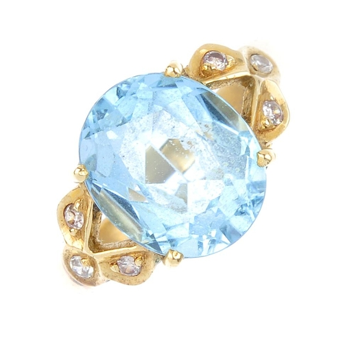 854 - A topaz and diamond dress ring. The oval-shape topaz, with single-cut diamond trefoil openwork sides...