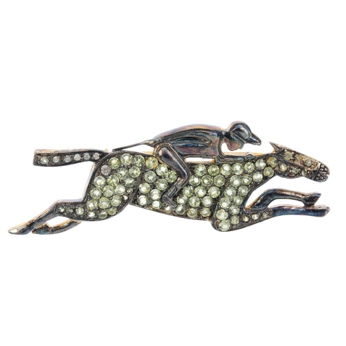 87 - A gem-set novelty brooch. The jockey, set atop a circular-shape yellow-gem galloping horse. Length 4...