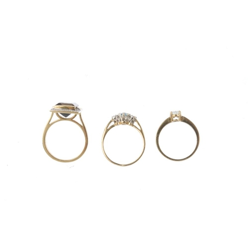 871 - Three 9ct gold gem-set dress rings. To include an aquamarine and diamond three-stone ring, a prasiol...