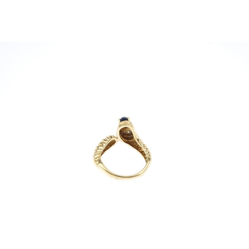 889 - A 14ct gold sapphire and diamond snake ring. The sapphire cabochon and pave-set diamond accents, to ...