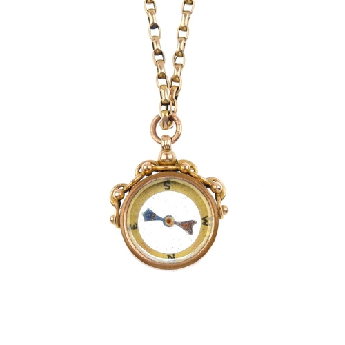 899 - An early 20th century 9ct gold compass pendant. Of circular-outline the yellow dial, with bead detai...