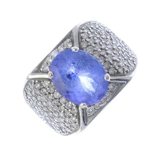 902 - A tanzanite and diamond dress ring. The oval-shape tanzanite, with pave-set diamond sides and bar ac...