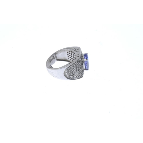 902 - A tanzanite and diamond dress ring. The oval-shape tanzanite, with pave-set diamond sides and bar ac...