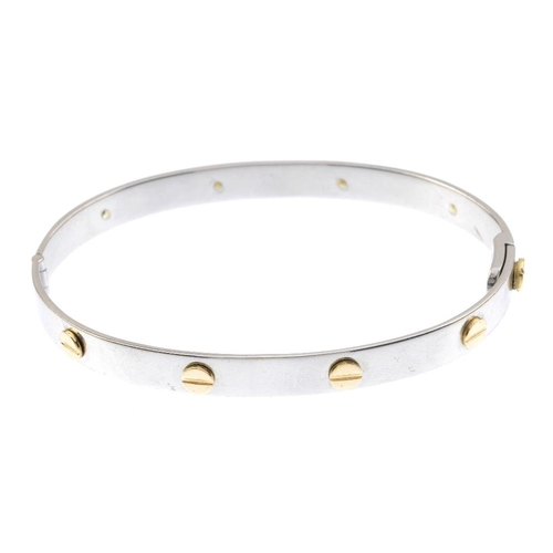 904 - A bangle. Of bi-colour design, the plain bangle, with raised screw motif and similarly-designed clas...